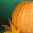 Ripe orange pumpkin with yellow autumn leaves on green background close-up — Stock Photo #13871548