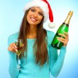 Beautiful young woman with bottle and glass of champagne, on blue backgroun - Lizenzfreies Foto