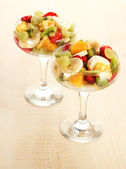 Fresh fruits salad on wooden table — Stock Photo