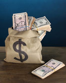 Bag with stacks of dollars on wooden table on blue background — Stock Photo
