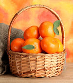 Tangerines with leaves in a beautiful basket, on wooden table — Stock Photo
