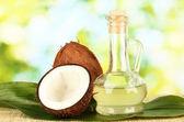 графин с кокосовым маслом и кокосы на зеленом фоне — Стоковое фото