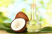 Decanter with coconut oil and coconuts on green background — Стоковое фото