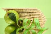 Leckeres knäckebrot, apfel und maßband auf grünem hintergrund — Stockfoto