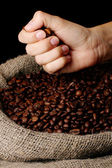 Coffee beans in hand on dark background — Stock Photo