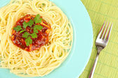 Italian spaghetti in plate on bamboo mat — Stock Photo
