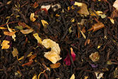 Aromatic black dry tea with fruits and petals, close up — Stock Photo