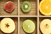 Sliced fruits in wooden box background — Stock Photo