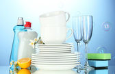 Empty clean plates and glasses with dishwashing liquid, sponges and lemon — Stock Photo