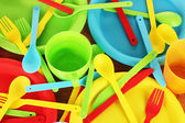 Bright plastic disposable tableware on wooden background close-up — Stock Photo