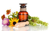 Medicine bottle with tablets and flowers isolated on white — Stock Photo