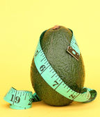 Avocado with measuring tape on yellow background — Stock Photo