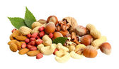 Assortment of tasty nuts with leaves, isolated on white — Stock Photo