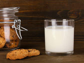 Glass of milk with cookies on wooden table close-up — Stock Photo