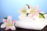 Stack of towels with pink lily on blue background — Stock Photo
