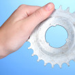 Man holding metallic cogwheel in his hand on blue background - Stock Photo