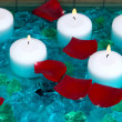 Beautiful candles in pool surrounded by rose petals close-up — Stock Photo
