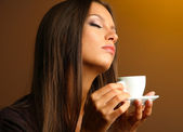 Beautiful young woman with cup of coffee, on yellow background — 图库照片