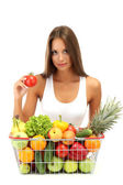 Beautiful young woman with fruits and vegetables in shopping basket, isolat — Stock Photo