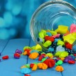 Scattered pieces of paper and colored stones with dreams in glass vase - Stock Photo