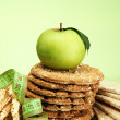 Tasty crispbread, apple, measuring tape and ears, on green background — Stock Photo