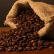 Coffee beans in bag on table on dark background - Stock Photo