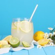 Citrus lemonade in glass bank of citrus around on wooden table on blue back — Stock Photo #13925097