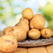 Ripe potatoes on wicker cradle on wooden table on natural background — Stock Photo #13925186