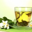 Cup of green tea with jasmine flowers on wooden table on green background — Stock Photo #13925795