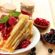leckere Pfannkuchen mit Beeren, Marmelade und Honig auf Holztisch — Stockfoto