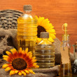 Oil in bottles, sunflowers and seeds, on wooden background — Zdjęcie stockowe