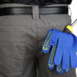 Gloves and instruments in back pocket close-up - Stock Photo