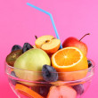 Glass bowl with fruit for diet on pink background - Foto Stock