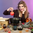 Halloween witch preparing poison soup in her cauldron on color background — Stock Photo #13927168