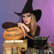 Halloween witch preparing poison soup in her cauldron on color background — Stock Photo #13927175