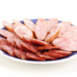 Tasty sliced sausage on plate isolated on white - Stock Photo
