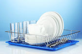 Clean dishes on stand on blue background — ストック写真