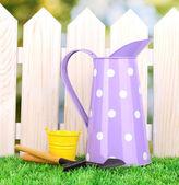 садовничая инструменты на зеленой траве на фоне деревянный забор — Стоковое фото