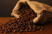 Coffee beans in bag on table on dark background — Stock Photo