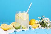 Cytrusowych lemoniady w banku szkła z owoców cytrusowych wokół na drewnianym stole na powrót niebieski — Zdjęcie stockowe