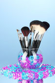 Make-up brushes in a bowl with stones on blue background — Stock Photo