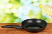 Leje olej w rondlu na drewnianym stole — Zdjęcie stockowe