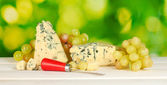 Composition of blue cheese and grapes on green background close-up — Stock Photo