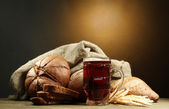 Tankard of kvass and rye breads with ears, on wooden table — Stock Photo