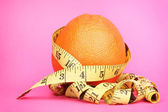 Orange with measuring tape on pink background — Stock Photo