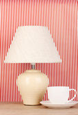 Table lamp and cup on striped background — Stockfoto
