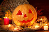 Halloween pumpkin and autumn leaves, on wooden background — Stock Photo