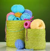 красочные пряжа для вязания в зеленой корзине на зеленом фоне — Стоковое фото