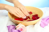 Woman hands with wooden bowl of water with petals, on blue background — Stock Photo