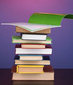 Stack of interesting books and magazines on wooden table on purple backgrou — Stock Photo
